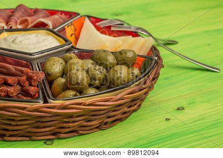 Basket With Several Spanish Tapas On Green Table