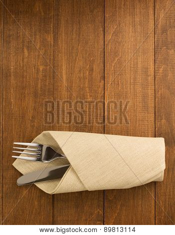 knife and fork at napkin on wooden background