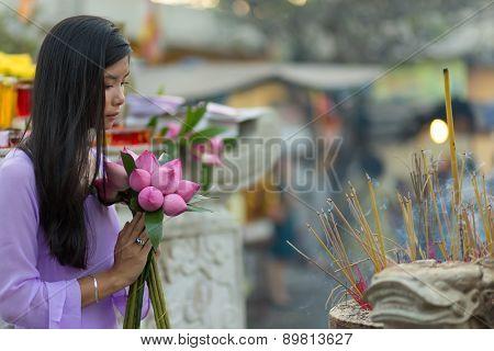 Vietnamese woman praying in temple, holding lotus flower buds bunch, Vietnam