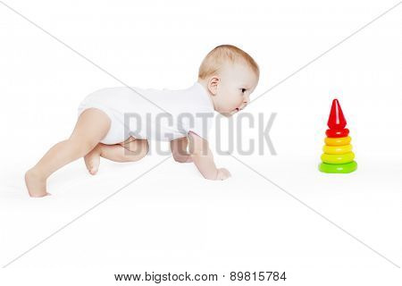 Happy cute laughing baby crawling to pyramid. Positive smiling  child. Smiling kid. Beautiful smiling cute funny baby. C�¡oncept of childhood, learning new