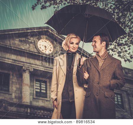 Elegant couple with umbrella against building facade