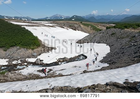Tourists Traverse Mountain River On Snowfield. Russia, Far East, Kamchatka Peninsula