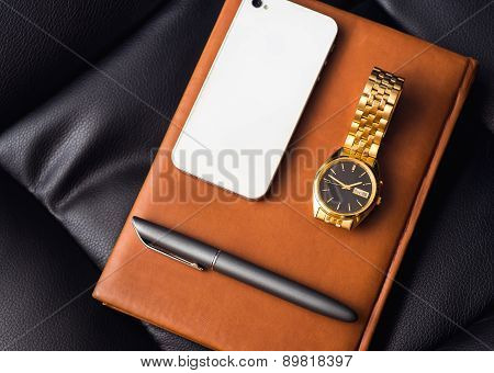 Men's accessory, golden watch, pen and mobile phone on the leather diary.
