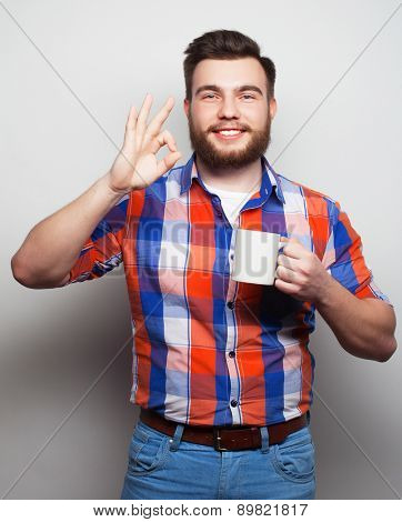 food, happiness and people concept: young bearded man with a cup of coffee against grey background