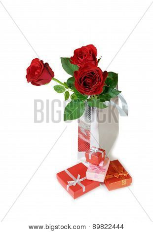 Three Red Roses In A Silver Gift Bag And Gift Boxes On White Background