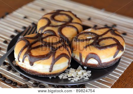 Three traditional donuts with chocolate on the brown plate