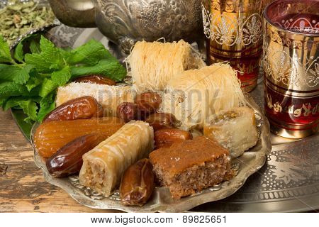 Oriental sweet cookies, tea cups and mint leaves on a Moroccan tea tray
