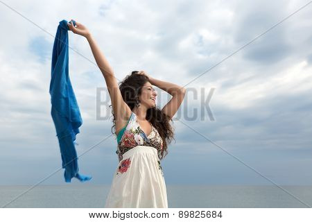 Attractive young woman on the beach waving with a blue scarf