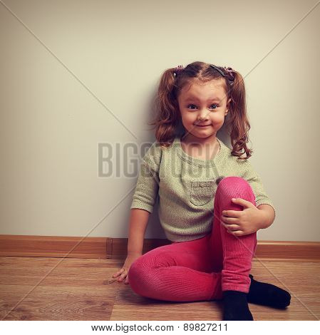 Grimacing Fashion Girl Sitting On The Floor And Smiling. Vintage Portrait