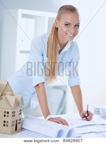 Portrait of female architect with blueprints at desk in office, isolated