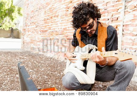 A street musician tuning his instrument