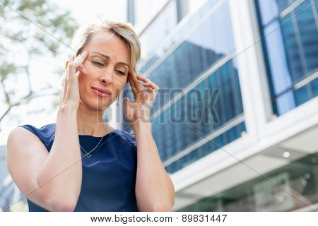 Businesswoman standing in street and trying to concentrate