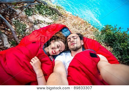 Young couple in sleeping bags near the sea