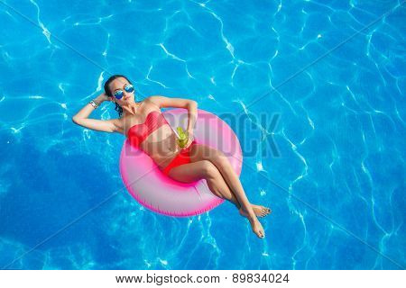 Beautiful girl in the pool on inflatable lifebuoy.