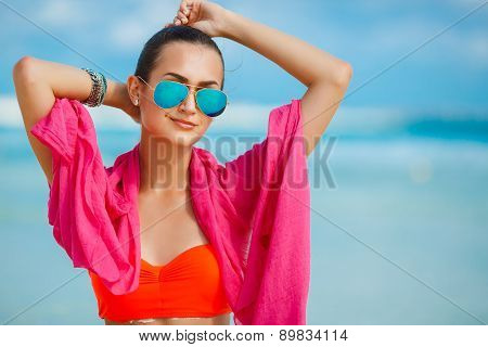 An attractive young woman on a tropical beach, enjoying the waves