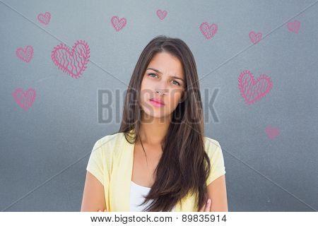 Frowning casual woman looking at camera against grey
