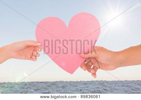 Couple passing a paper heart against horizon over the sand