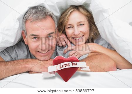 Loving couple under the duvet against heart with scroll