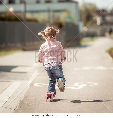 Two years old girl riding her scooter on the street. back  view