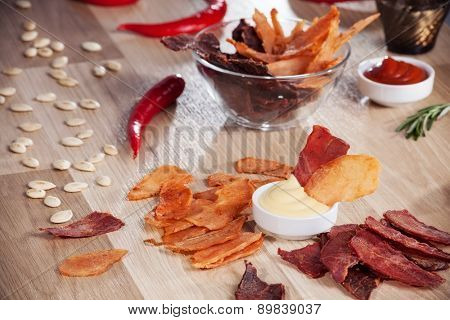 meat chips on a plate with pepper pumpkin seeds and pepper