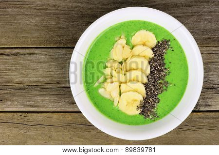Green smoothie bowl on a wood background