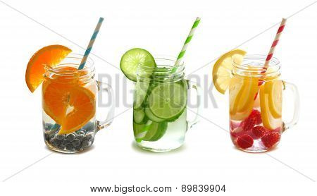 Detox fruit water in mason jars with straws isolated