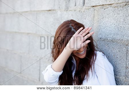 Shy brunette girl covering her face with a grey wall of background