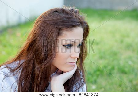 Sad brunette woman in park thinking something