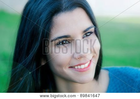 Happy brunette girl smiling in the field