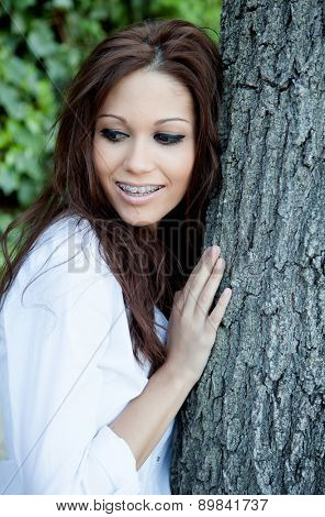 Portrait of a beautiful brunette girl next to a tree