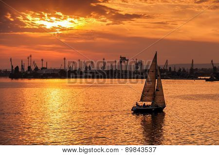 Sailing Yacht Enters Varna Harbor At The Sunset