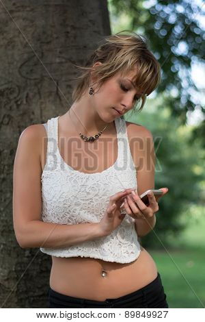 Attractive blonde young woman outdoors using cell phone