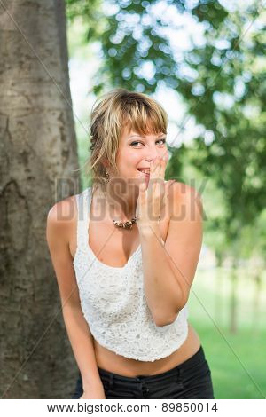 Blonde young woman outdoors laughing and hiding mouth