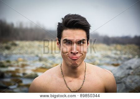 Shirtless young man outdoor doing silly face
