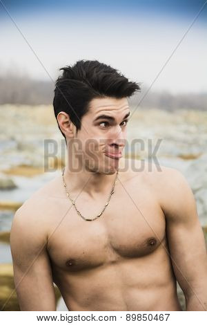 Shirtless young man outdoor doing silly face and stupid expression