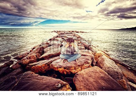 desperate man sit on sea rock