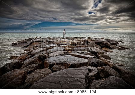 standing businessman on sea rock