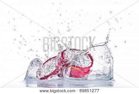 Fresh dragon fruit in water splash isolated on white background