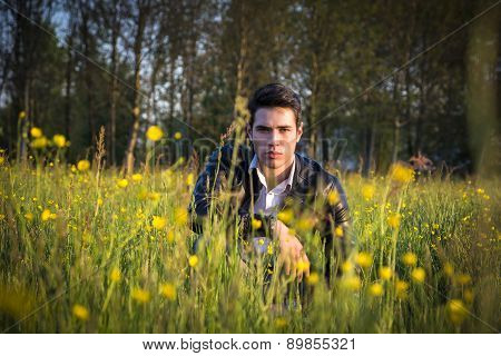 Handsome sexy man outdoors in the garden crouching down on grass