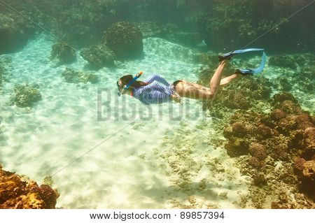 Woman with mask snorkeling in clear water