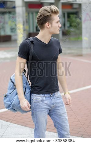 Attractive young man with backpack standing outside