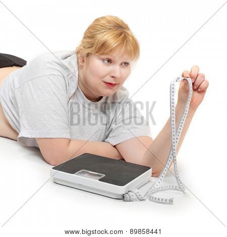 Depressed woman with measure tape and weight scale.