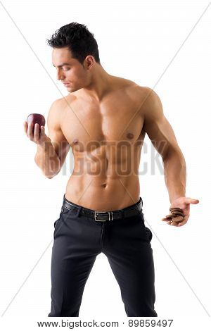 Muscular man deciding between healthy fruit and cookies