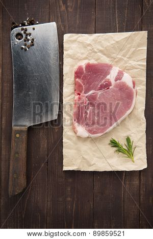 Raw Pork Chop Steak And Cleaver On Wooden Background