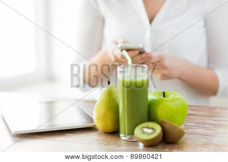 healthy eating, technology, diet and people concept - close up of woman hands holding smartphone with tablet pc, fruits and fresh juice sitting at table