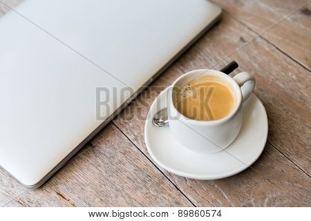 technology, business and modern life concept- close up of open laptop computer and coffee cup on table at office or hotel room