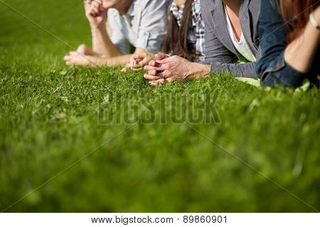 summer holidays, friendship, leisure and teenage concept - close up of students or teenagers lying on grass and hanging out at campus or park