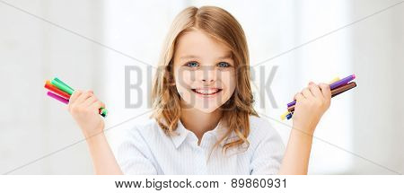 education, creation and school concept - smiling little student girl showing colorful felt-tip pens at school