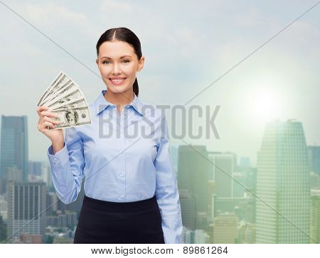 business and money concept - young businesswoman with dollar cash money over city background
