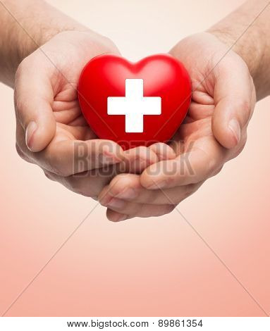 family health, charity and medicine concept - close up of male hands holding red heart with white cross over beige background